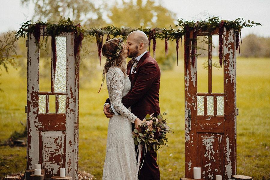 pocałunek młodej pary podczas ceremonii zaślubin zorganizowanej w plenerze